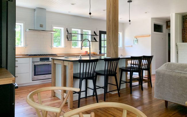 large open concept kitchen with large kitchen island and bar seating, bright white and light woods