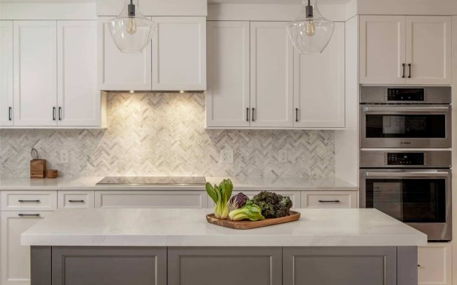 modern light kitchen remodel with white cabinets, functional kitchen island, and modern pendant lighting