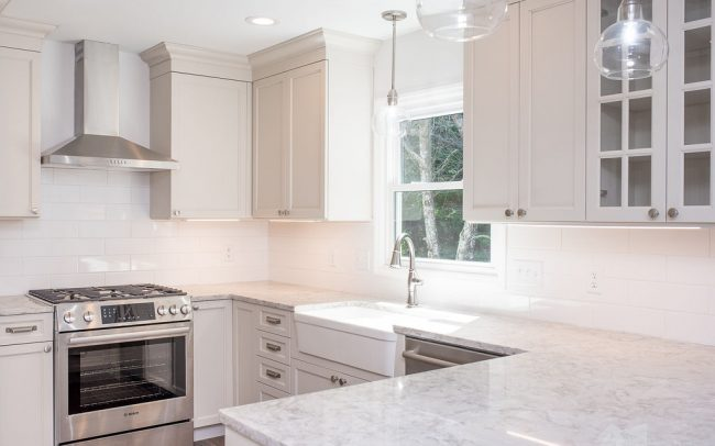 subway tile backsplach, oven hood, custom kitchen cabinets and apron sink in kitchen makeover